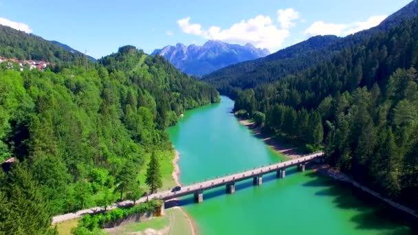 picturesque aerial view of bridge over clean blue river, hills covered with evergreen forest
