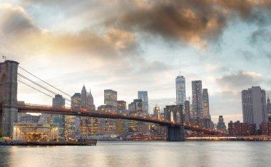 Manhattan skyline and Brooklyn Bridge view from Brooklyn Bridge Park at sunset, New York City.
