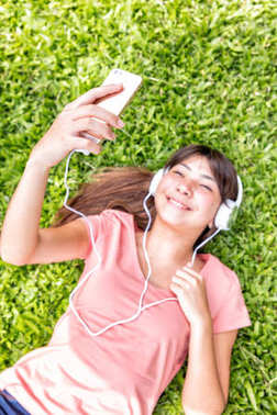 Asian girl hearing music laying on the grass. Focus on smartphon