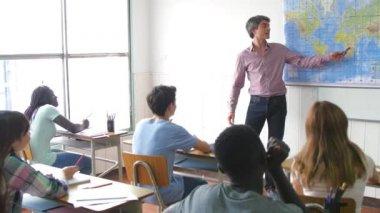 Teacher explaining lesson to positive pupils in a multi ethnic t