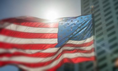 USA flag. American flag with blowing wind. Cityscape background.