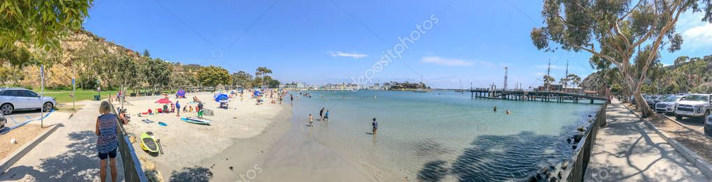 DANA POINT, CA - JULY 31, 2017: Tourists visit city beach on a windy summer day. Dana Point is a tourist attraction in California.