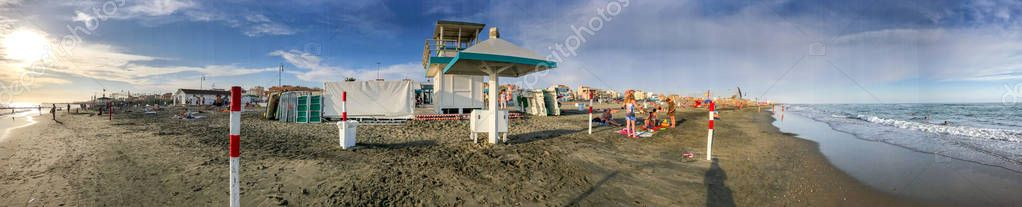 LIDO DI OSTIA, ITALY - JULY 26, 2017: Tourists and locals on the beach at sunset. Lido di Ostia is a famous tourist destination.