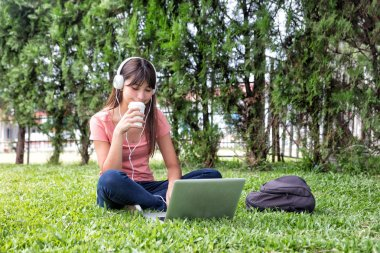 Asian girl on the grass using laptop and hearing music.