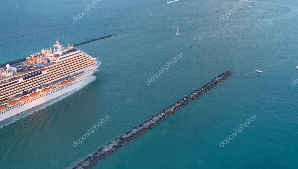 Departing cruise ship at sunset, aerial view.