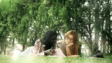 couple of mixed race female teenagers lying on grass with notebooks