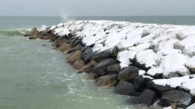 amazing winter seascape with rocks, covered with snow