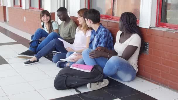 Happy bteenagers sedí na podlaze na školní chodbě