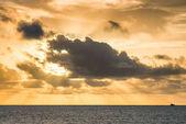 Úžasný západ slunce nad oceánem, slunce zakryto husté mraky, filtrování paprsky
