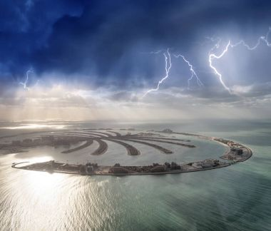 Amazing aerial view of Palm Jumeirah Island in Dubai from helicopter against sunset sky.
