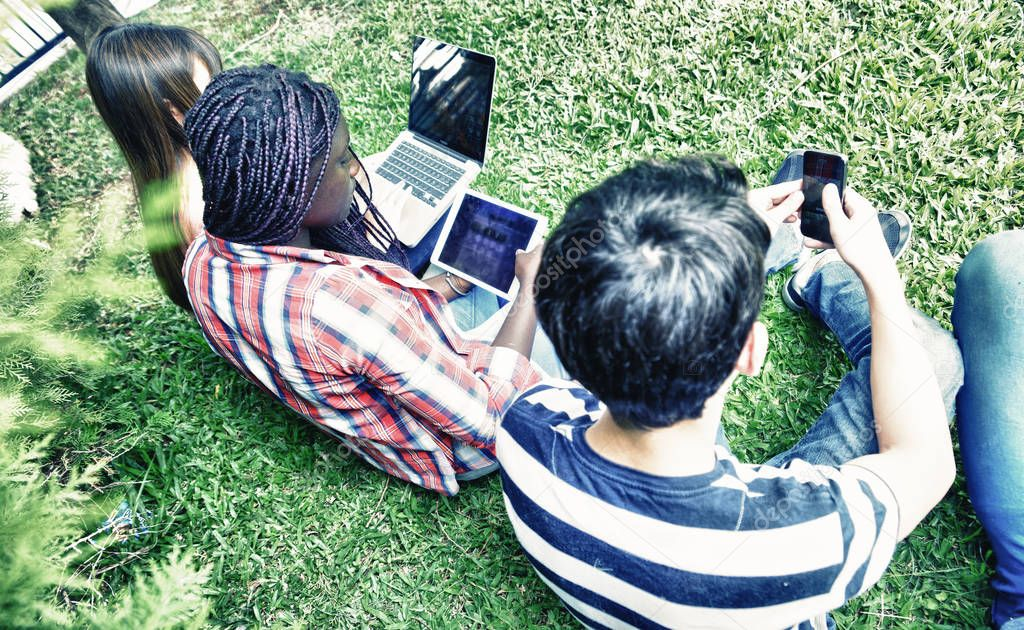 Multi ethnic teenagers friends using electronics gadgets, seated on a park.