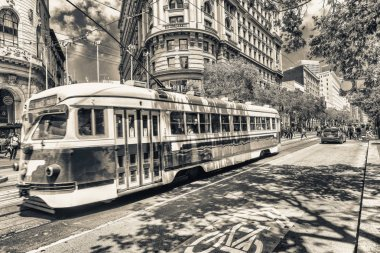 SAN FRANCISCO, CA - AUGUST 6, 2017: Red tram along city streets. San Francisco attracts 30 million people annually.