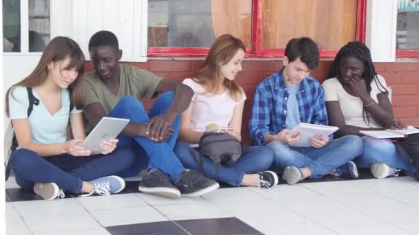 group of teenagers sitting in school hallway and studying