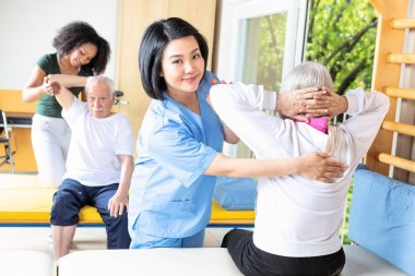 Asian and african nurses helping elder couple at rehab facility gym.