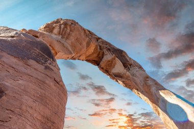 Skyward view of Delicate Arch, Arches National Park. Rock formation and blue sky, USA