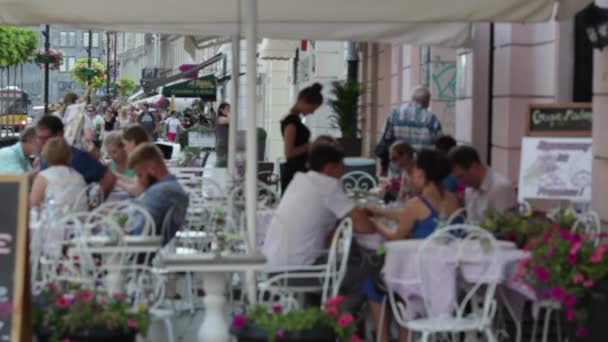 People sit in a cafe on a street terrace. Sunny summer day, people are relaxing in the cafe under umbrellas. People relax rest in a street cafe. People sitting in cafes. Sunny summer day. In Blurs