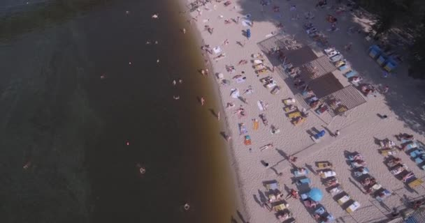 aerial of the beach. summer sunny day, people are sunbathing on a yellow squeak on the bank of the Dnieper river city of Kiev. day off, vacation on the beach. a large number of tourists swim.