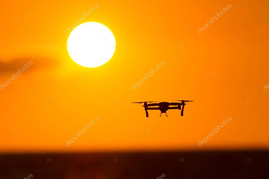 Drone flying over sunset sky