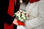 Zimní kytice v rukou nevěsty a ženicha