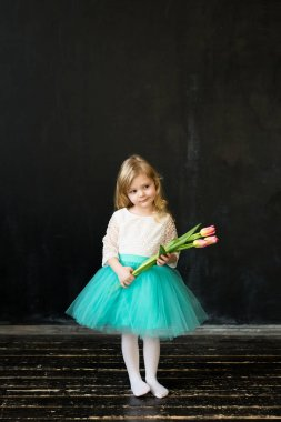 Beautiful girl with tulips on a black background