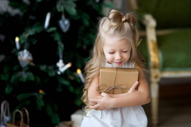 Happy cute little smiling girl with christmas gift box. Merry Christmas and Happy Holidays.