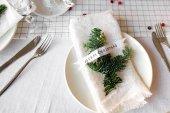 Vánoční stůl: nůž a vidličku, ubrousek a vánoční stromek větve na dřevěný stůl. Nový rok výzdobu svátečního stolu