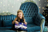portrait of beautiful smiling little girl with gift box sitting on vintage sofa near decorated Christmas tree. Merry Christmas and Happy Holidays
