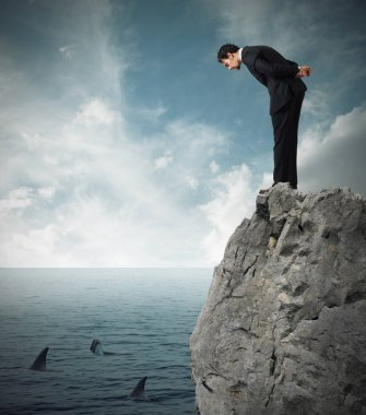 Businessman watching from a cliff