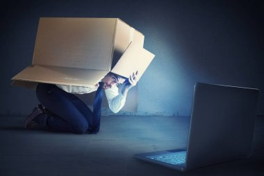 Afraid businessman hidden inside a cardboard