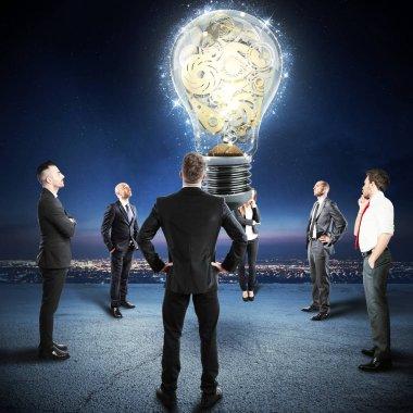 businesspeople watch a big lightbulb