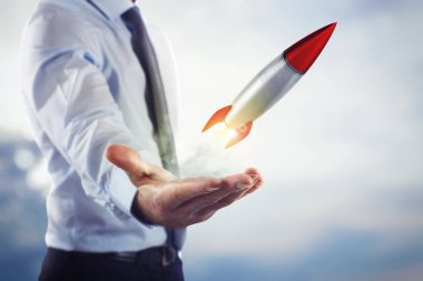 Businessman holding a small rocket
