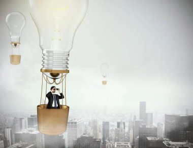 Balloon bulb flying  in the sky with businessman