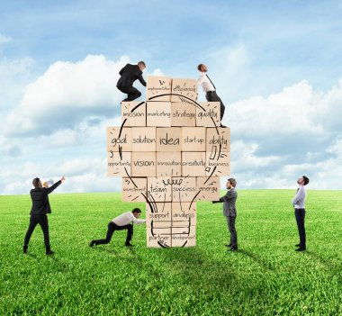 Businesspeople  build  together a big brick wall