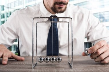 Businessman plays with the pendulum
