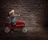 Fotografie Kind, das mit seinem Auto Spielzeug