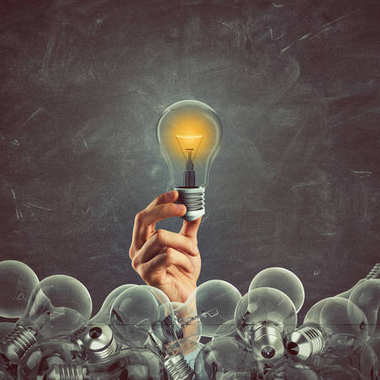 Bright bulb lit between unlit bulbs.
