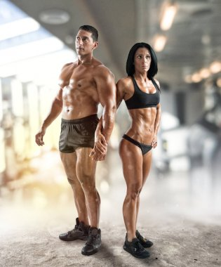 Muscled man and woman at the gym
