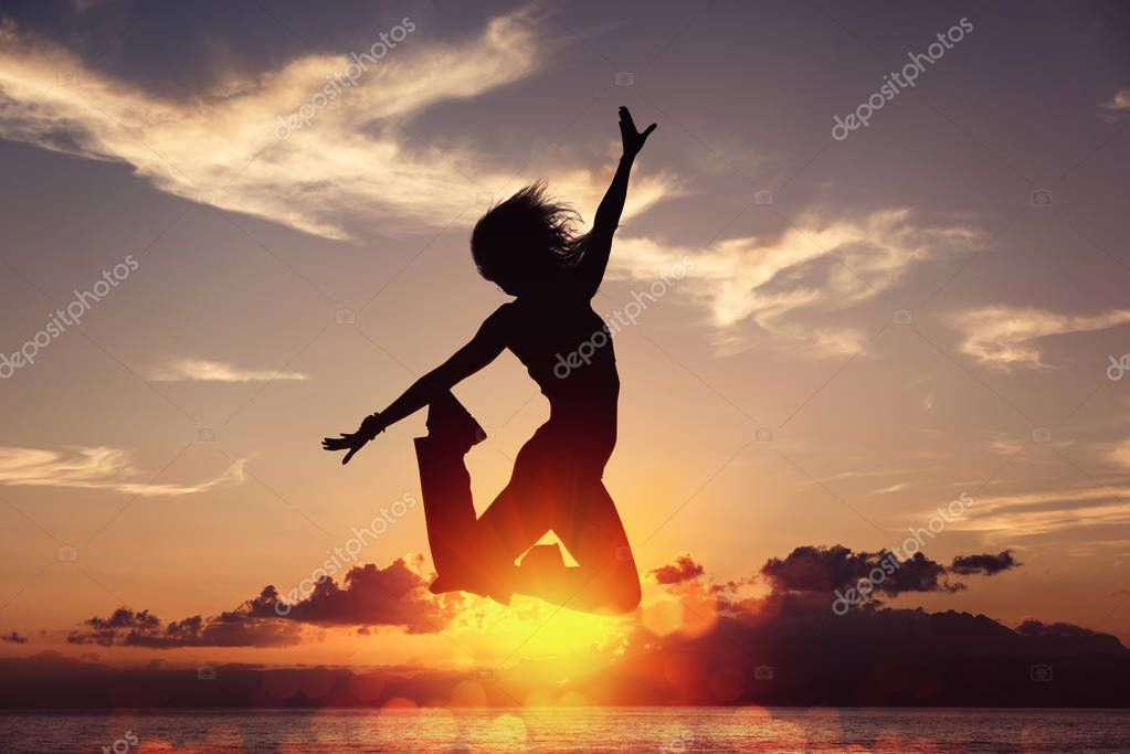 Silhouette of happy joyful woman jumping and having fun at the beach against the sunset. Concept of freedom and leisure vacation