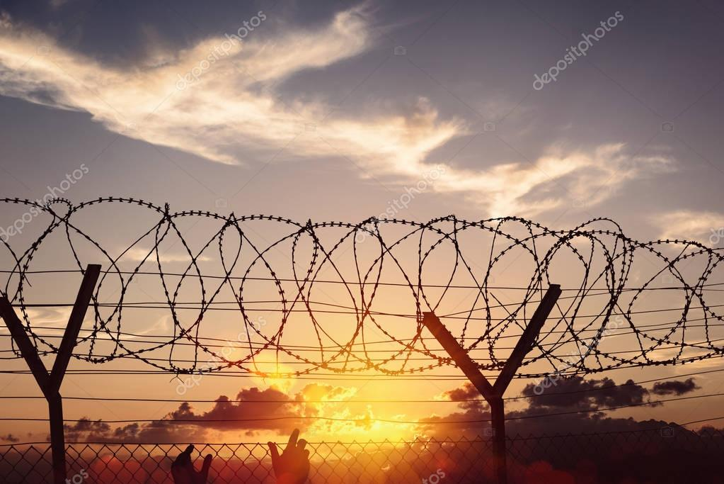 Silhouette of two hands on a fence at sunset