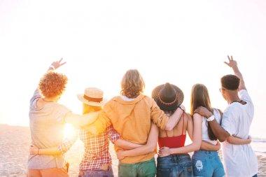 Group of happy friends having fun at ocean beach at dawn stock vector