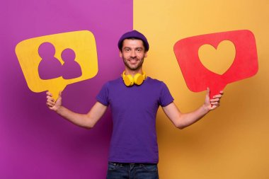 Man is happy because receives hearts and new friends from social network. Violet and yellow background