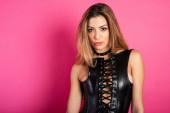 sinnliche Provokation einer sexy BDSM-Frau in Dessous mit Peitsche. Fuchsien-Hintergrund