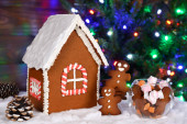 The hand-made eatable gingerbread house, little men and candy, New Year Tree with garland in background
