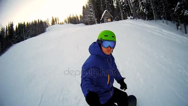 Mann fährt auf Snowboard mit Selfie-Stick in der Hand