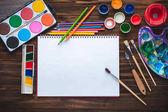 Satz von Farben, Stifte, Werkzeuge für Malerei und leeres weißes Papierblatt Skizzenbuch auf Vintage Holz-Hintergrund. Ansicht von oben