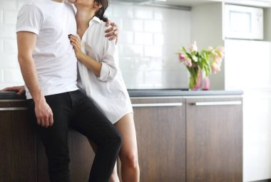 Young couple kisses and hugs at kitchen in the morning