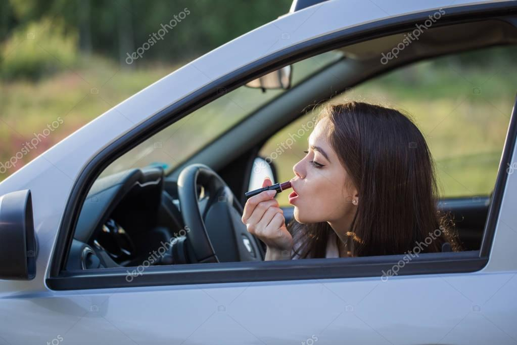 Girl paints her lips in the car