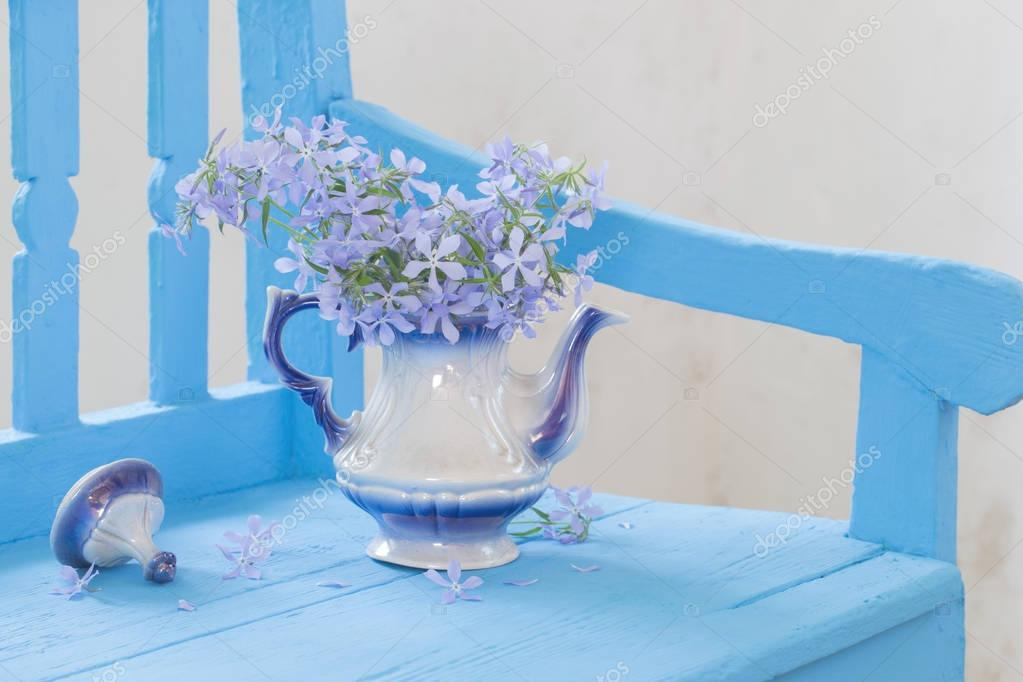 still life with spring flowers on blue bench