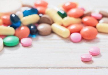 different  pills  mix  on white wooden background