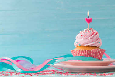 pink cupcake on blue wooden background
